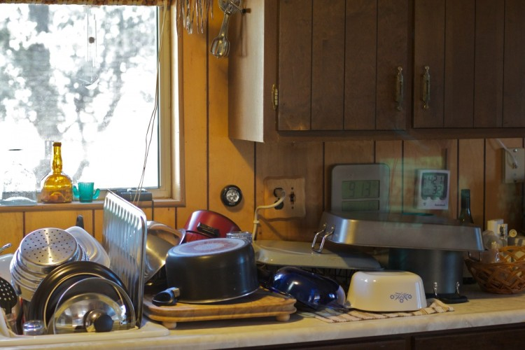 Dirty dishes on sink counter in kitchen near kitchen window