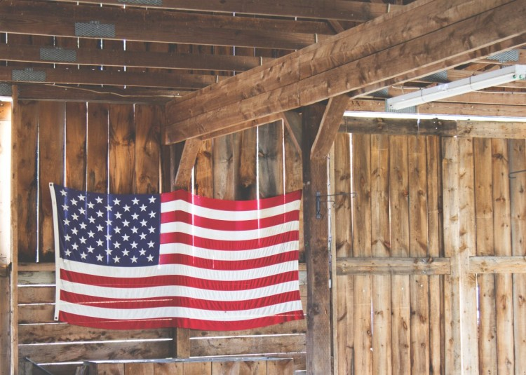 American flag hanging in barn with brown wood