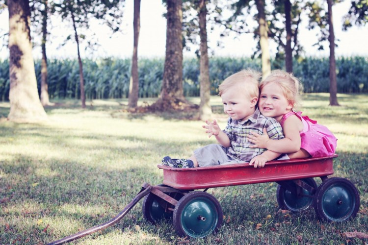 blond boy and blond girl smiling and sitting in red wagon on grass with trees in the background