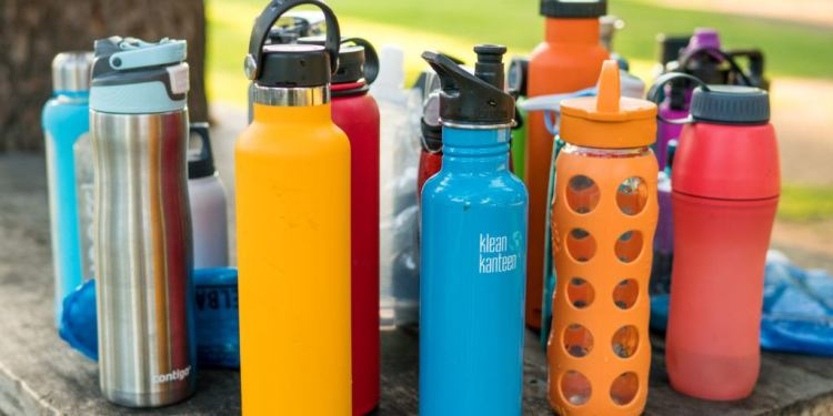 many types of water bottles sitting on a picnic table, colorful water bottles