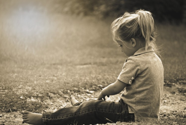 blond little girl with collared shirt sitting on ground, sepia filter