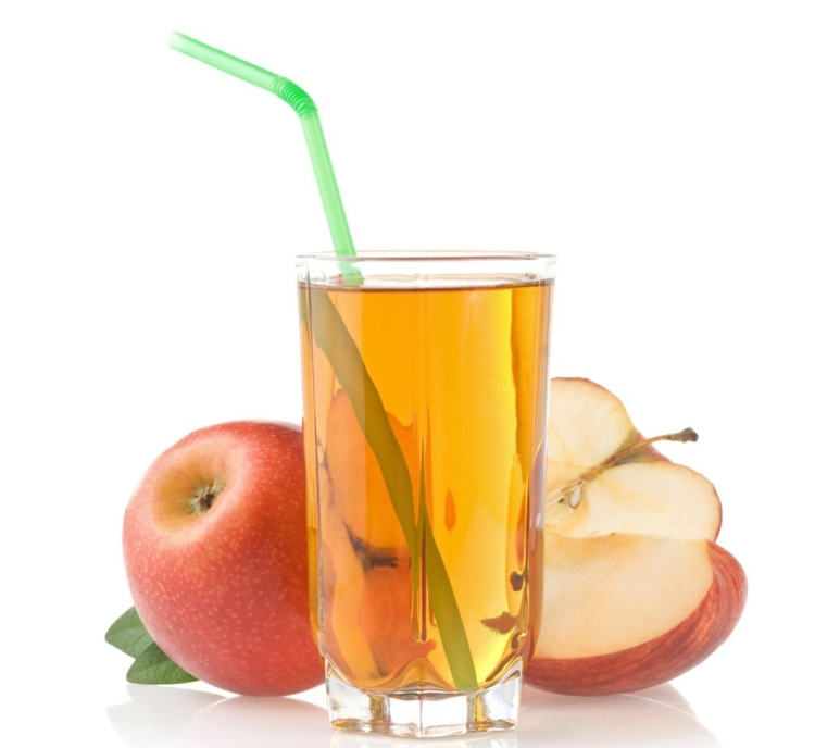 glass of apple juice with straw surrounded by apples
